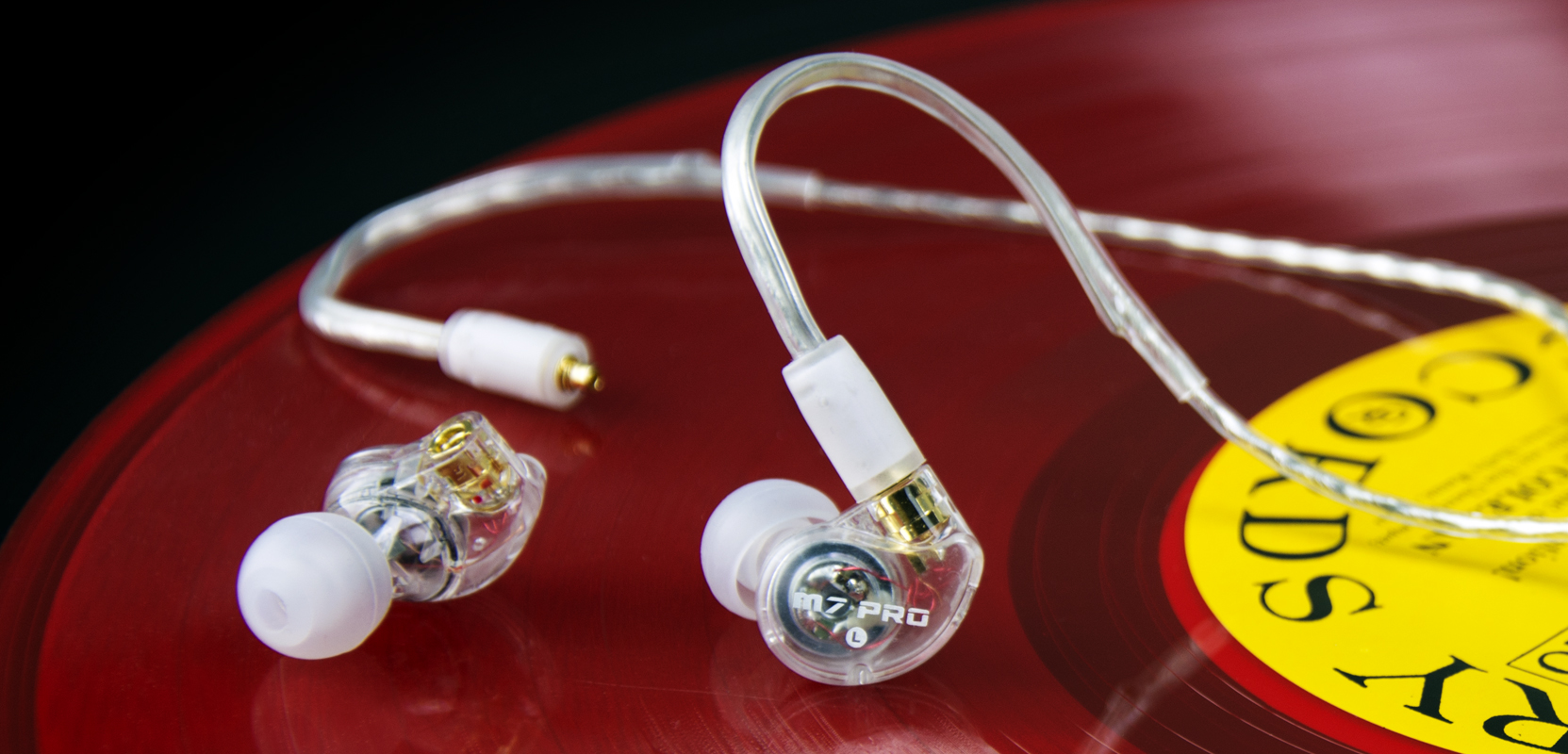 In ear monitors with one detached cable on a red vinyl record background